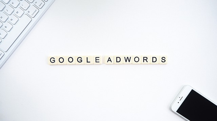 A white background showing a PC keyboard, a mobile phone, and words spelling out Google Adwords in the middle.